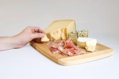 Olika typer av ost på en träbakgrund Arkivfoto