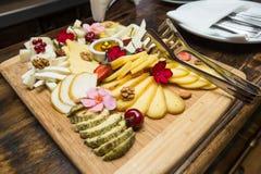 Olika typer av ost på en träbakgrund Arkivbilder