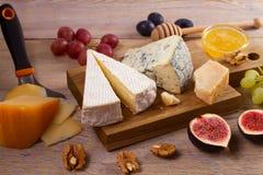 Olika typer av ost på en träbakgrund Olika typer av ost med druvor, honung, fikonträd och muttrar på den lantliga trätabellen Fotografering för Bildbyråer