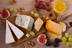 Olika typer av ost på en träbakgrund Olika typer av ost med druvor, honung, fikonträd och muttrar på den lantliga trätabellen Arkivfoton