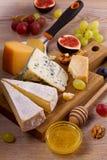Olika typer av ost på en träbakgrund Olika typer av ost med druvor, honung, fikonträd och muttrar på den lantliga trätabellen Royaltyfri Foto