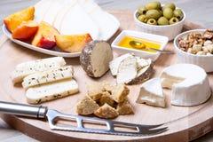 Olika typer av ost på en träbakgrund 4 typer av ost, melon, nektarin, muttrar, oliv Arkivfoton