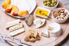 Olika typer av ost på en träbakgrund 4 typer av ost, melon, nektarin, muttrar, oliv Arkivbild