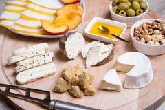 Olika typer av ost på en träbakgrund 4 typer av ost, melon, nektarin, muttrar, oliv Arkivbilder