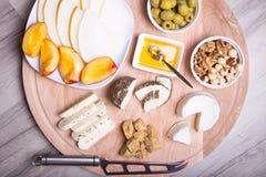 Olika typer av ost på en träbakgrund 4 typer av ost, melon, nektarin, muttrar, oliv Royaltyfria Bilder