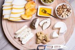 Olika typer av ost på en träbakgrund 4 typer av ost, melon, nektarin, muttrar, oliv Arkivfoto