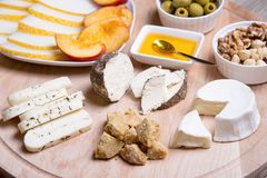 Olika typer av ost på en träbakgrund 4 typer av ost, melon, nektarin, muttrar, oliv Fotografering för Bildbyråer