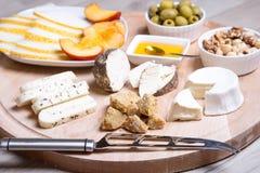 Olika typer av ost på en träbakgrund 4 typer av ost, melon, nektarin, muttrar, oliv Royaltyfri Fotografi