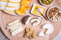 Olika typer av ost på en träbakgrund 4 typer av ost, melon, nektarin, muttrar, oliv Royaltyfria Foton