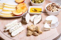 Olika typer av ost på en träbakgrund 4 typer av ost, melon, nektarin, muttrar, oliv Royaltyfri Bild