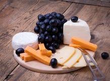 Olika typer av ost på träbakgrund Fotografering för Bildbyråer