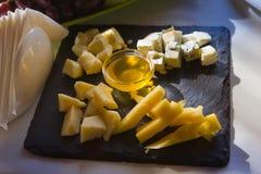 Olika typer av ost tjänade som på träplattan för den svarta fyrkanten, i panelljus, med honung, det nya läckra matfotoet Royaltyfria Bilder