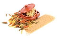 Olika typer av pasta och en lera lägger in Arkivfoton