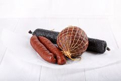 Olika typer av rökte salamikorvar på vit royaltyfria foton