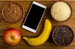 Olika typer av ris, smartphonen, äpplet och bananen på en woode Royaltyfri Fotografi
