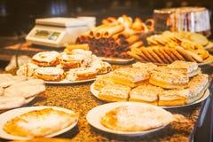 Olika typer av sötsakbakelser på plattor Royaltyfri Bild