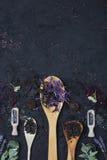 Olika typer av te som framläggas i trä- och silverskedarna arkivfoto