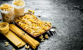 Olika typer av torr pasta p? plattan och i bunkar royaltyfri fotografi