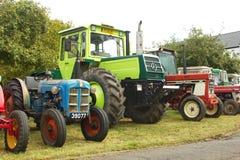 Olika typer av traktorer som arrangera i rak linje på `en, möter traktor`en även i Contern, Luxembourg Arkivfoton