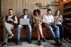 Olika ungdomarsom sitter i raden som hemsökas med online-apparater arkivfoto
