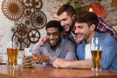 Olika vänner som håller ögonen på video på smartphonen och dricker öl arkivbild