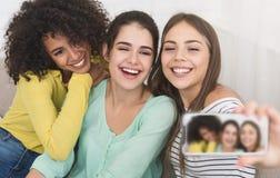 Olika vänner som hemma gör foto på smartphonen royaltyfria foton