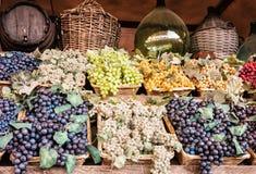 Olika variationer av druvor i de vide- korgarna, marknadsplac royaltyfri foto