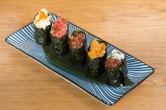 Olika variationer av gunkan som slås in i norihavsväxt, tartare bluefintonfisk, kaviaren av olika format och färgavokadot, hav arkivfoto