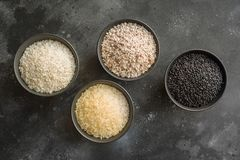 Olika variationer av ris Svarta ris i bunke på svart Top beskådar arkivfoton