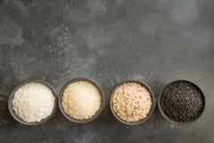 Olika variationer av ris Svarta ris i bunke på svart Top beskådar arkivfoto