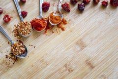 Olika varma kryddor på en träbakgrund Arkivfoto