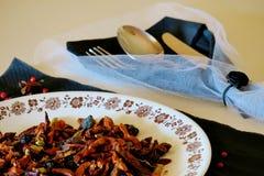 Olika varma kryddor p? en vit platta bredvid en k?ksked, gaffel och kniv arkivbild