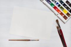 Olika vattenfärgmålarpenslar med färger och papper Arkivfoto