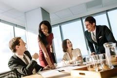 Olikt affärsfolk som ler under ett möte arkivbilder