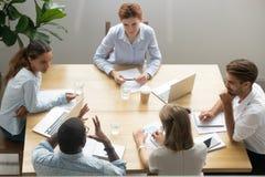 Olikt affärslag som lyssnar till ledaren på möte, bästa sikt royaltyfri fotografi