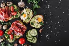 Olikt av smörgåsar och bruschetta med prosciuttoen, det stekte vaktelägget, avokadot, gurkan, tomater, kryddor och gräsplaner Royaltyfri Foto