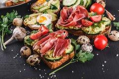 Olikt av smörgåsar och bruschetta med prosciuttoen, stekt quaiVarious av smörgåsar och bruschetta med prosciuttoen, stekt vaktel Royaltyfri Fotografi