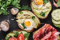 Olikt av smörgåsar och bruschetta med prosciuttoen, stekt vaktelägg, avokado, gurka, tomater Arkivfoto