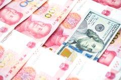 Olikt begrepp med US dollarräkningen i hög av kinesisk yuanbi Royaltyfri Fotografi