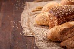 Olikt bröd på säckväv på trätabellnärbilden Arkivfoton