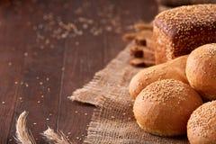 Olikt bröd på säckväv på trätabellnärbilden Royaltyfri Foto
