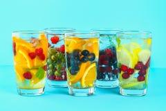 Olikt detoxvatten i exponeringsglas, olika smaker, bär, frukter arkivbilder