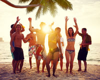 Olikt folk som dansar och festar på en tropisk strand arkivbilder