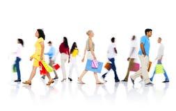 Olikt folk som går med shoppingpåsen royaltyfria foton
