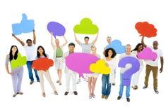 Olikt folk som rymmer den färgrika anförandebubblan Arkivbild