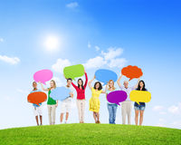 Olikt folk som rymmer färgrika anförandebubblor Arkivbild