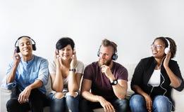 Olikt folk som sitter på den bärande hörlurar för soffa royaltyfri fotografi