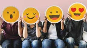 Olikt folk som täckas med emoticons Arkivbild