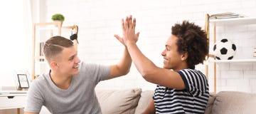 Olikt ge sig för vänner som är högt-fem, medan spela fotbollleken på konsolen royaltyfri foto