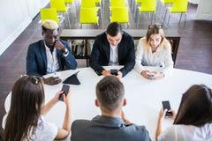 Olikt kontorsfolk som arbetar på mobiltelefoner Företags anställda som rymmer smartphones på möte Allvarligt blandras- royaltyfria foton